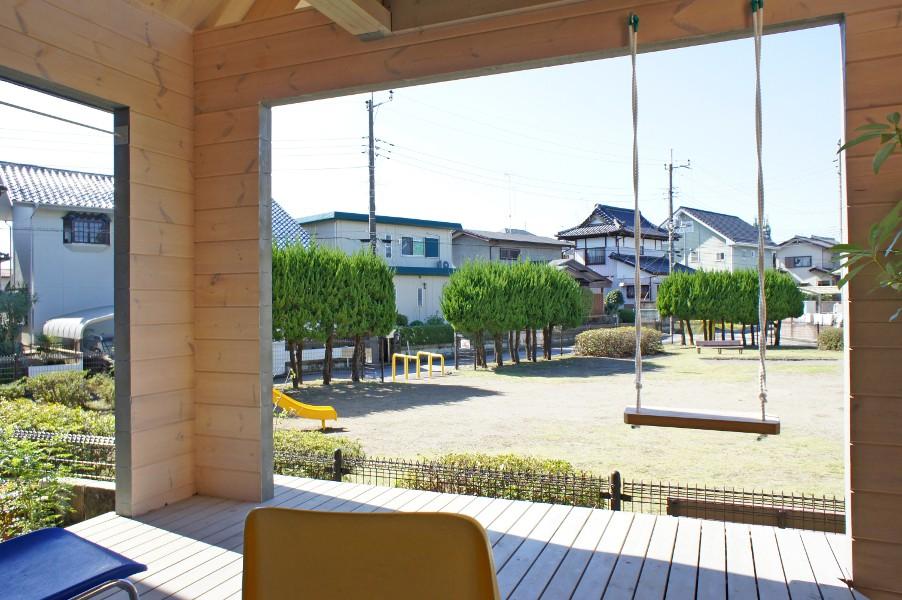 デザイナーズログハウスの1階半屋内テラスから借景の公園を望む