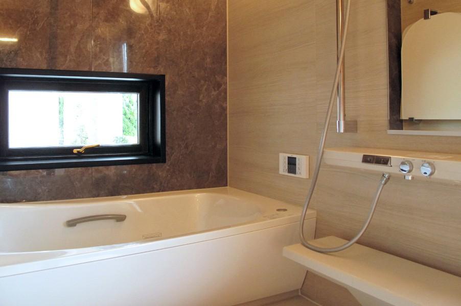 外まで広がるガラス貼りの1.25坪ユニットバスです。空間の広がりはリゾートホテルの大型浴室空間です。